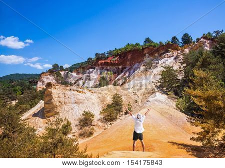 Elderly man admires a magnificent landscape. Orange and red picturesque hills in Roussillon