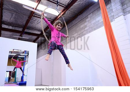 Little Child Learn Circus Skills On Aerial Lyra