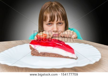 Young woman cannot resist the temptation and wants to eat sweet cake - diet concept