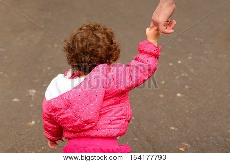 Toddler child girl age one two (1-2) years hold hands and walks on a path in the park with her mother.Children concept Horizontal Copy Space