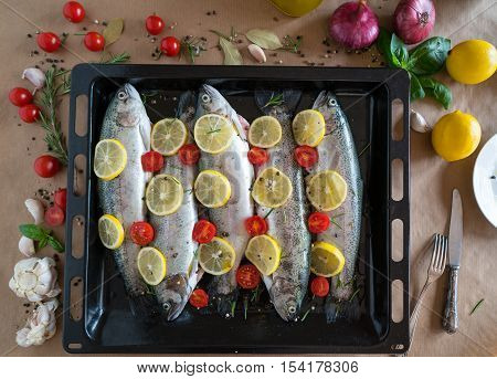 fresh trout fish on a baking sheet and surrounded by vegetables and spices