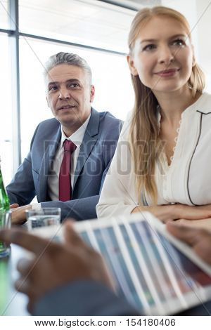 Mature businessman with female colleague at table in meeting room