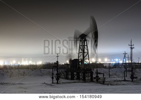 Working oil pump jack at night time. Oilfield during winter. Refinery lights background. Oil and gas concept.