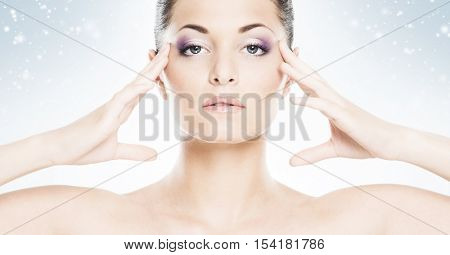 Face of attractive and healthy woman over seasonal Christmas background with a winter snowflakes. Healthcare, spa, makeup and face lifting concept.