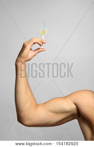 Sportsman hand holding syringe on light background
