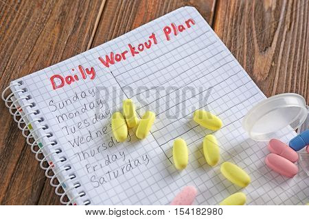 Notebook and drugs on wooden background