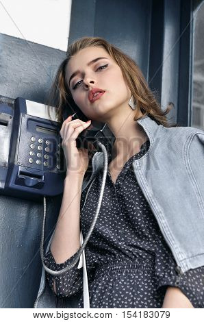 Pretty Girl Languidly Talking On A Pay Phone