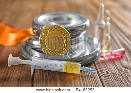 Syringe, medal and weight disks on wooden background