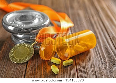 Drugs, medal and weight disks on wooden background