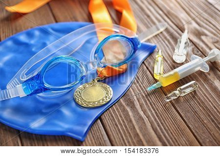 Sports equipment and syringe on wooden background