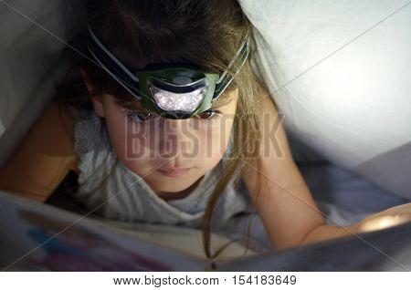 Little Child Read Book In Bed Under The Covers At Night