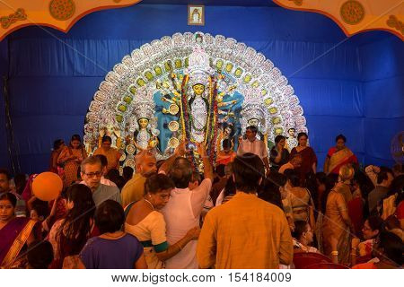 KOLKATA, INDIA - OCTOBER 9, 2016:Crowd gathered inside a Durga Puja pandal to offer prayer to Goddess Durga on Ashtami day at a Durga pandal in South Kolkata, West Bengal, India.