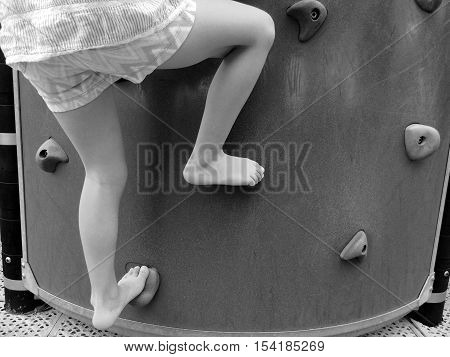 Child Climbing On A Playground Rock Wall