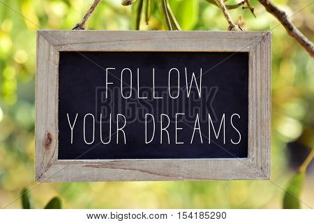 a wooden framed chalkboard with the text follow your dreams hanging from the branch of a tree