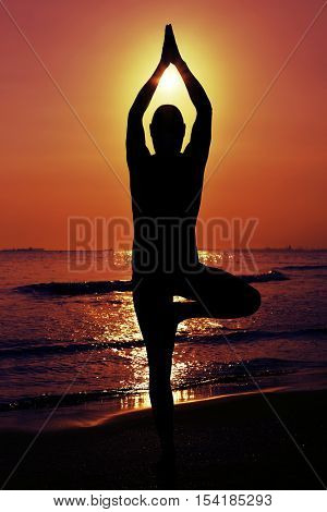 the silhouette of a young yogi man practicing the tree pose in front of the sea in backlight