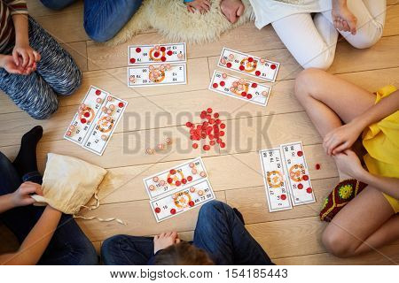 Children play russian lotto sitting on the floor, view from above.