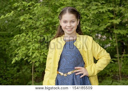 Half-length portrait of smiling girl in yellow jacket in green park.