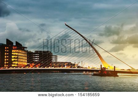 Samuel Becket Bridge at sunset in Dublin, Ireland. Beautiful architecture and illuminated hotels