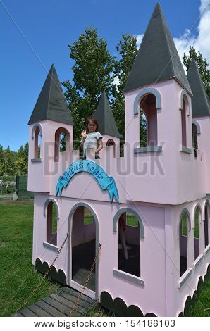 Little girl age (5-6) play pretend to be a princes in outdoor playground princes castle.