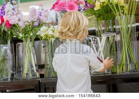 Kid boy shopping in a flower shop. cute little boy on shopping.