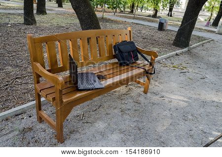 Open laptop computer, bag and phone  on  wooden bench in the park, Sofia, Bulgaria