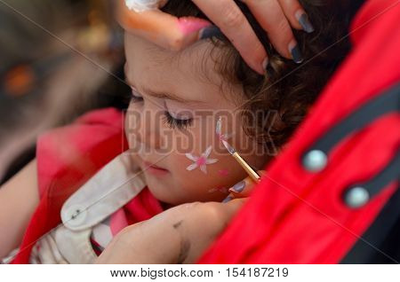 Toddler girl (age 1-2) getting her face painted with flowers by face painting artist.