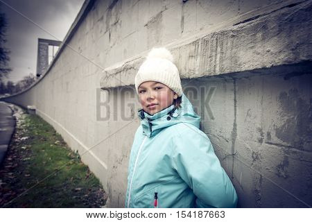 Girl teenager in a knitted cap and warm jacket standing near the concrete wall. Street Photography.