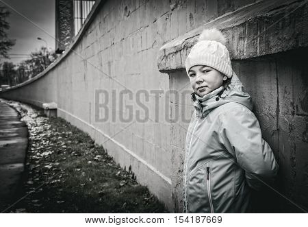 Girl teenager in a knitted cap and warm jacket standing near the concrete wall. Street Photography. Black and white monochrome image