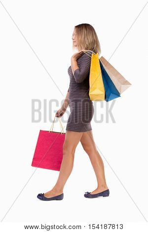 back view of going  woman  with shopping bags . beautiful girl in motion.  backside view person. Isolated over white background. Girl in brown dress is laying over the shoulder bags with purchases