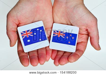 Two hands holds the national flags of Australia (R) and New Zealand (L) beside each other on a white background. Foreign relationship policy concept