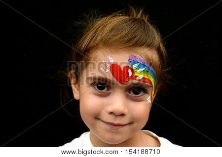Little girl with face painted with rainbow.