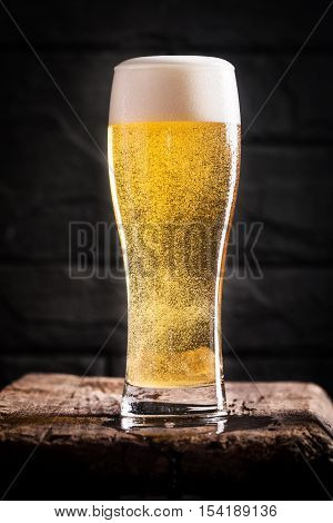 Glass of light beer with bubbles near black wall