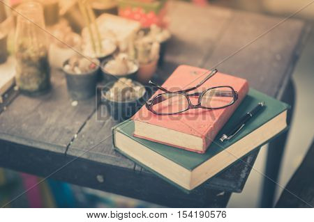 Glasses with books and pen on wood table in morning time. weekend lifestyle concept with vintage filter effect