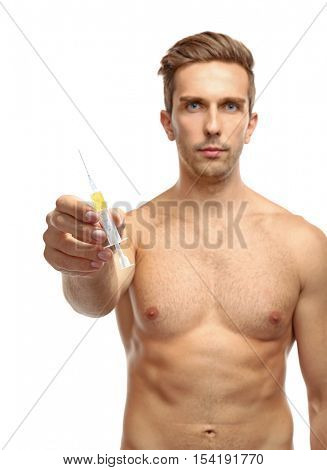 Muscular man holding syringe on white background