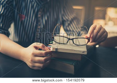 Morning lifestyle scene of young hipster woman put her glasses down on books stack in cafe. Weekend activity or hobby concept with vintage filter effect