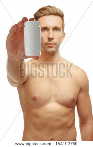 Muscular man holding drugs on white background