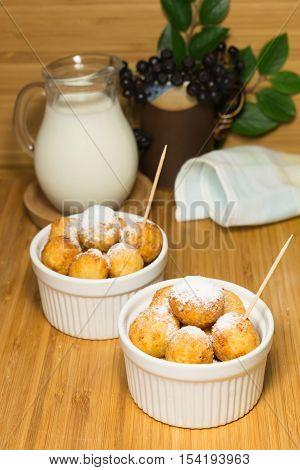 Cottage cheese fried balls in ceramic ramekin with milk