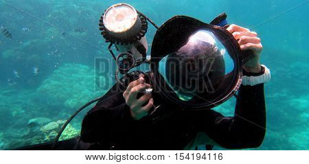 Underwater photographer photographing with a camera underwater
