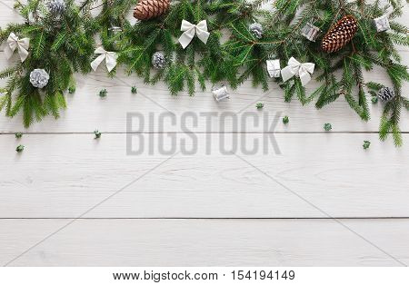 Christmas decoration, stars and garland frame concept background, top view with copy space on white wood table surface. Christmas ornaments border with fir tree branches and bows