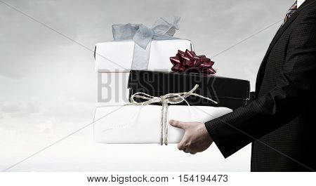 Businessman hold gift box . Mixed media