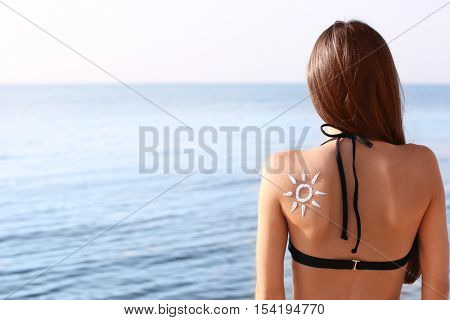 Young woman with sunscreen on back,  sea background
