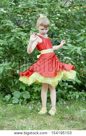 Little girl dressed in red gown with yellow underskirt spins standing outdoor.