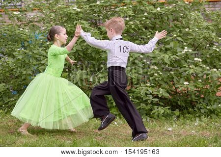 Children couple dances ballroom dance outdoor at grassy lawn.