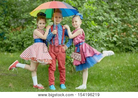 Boy in red trousers and blue shirt stands with two girls under coloured rainbow umbrella at grassy lawn.