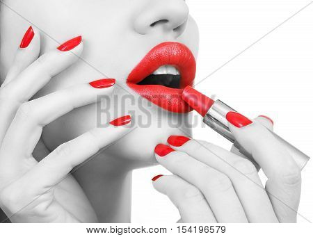 Black and White female Portrait with Red lips. Sexy Young Beautiful Girl with Red Nails applies red lipstick. Female Glamour portrait sensual bright Make-up and Manicure closeup. White background
