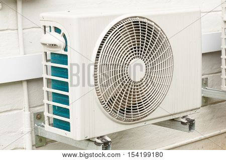 Weathered White Airconditioning Unit Mounted On Exterior Home Wall