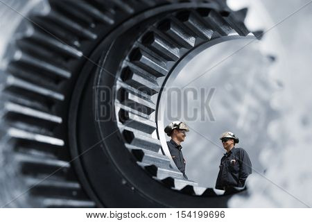 industrial workers inside giant cogwheels and gears axle, steel industry works