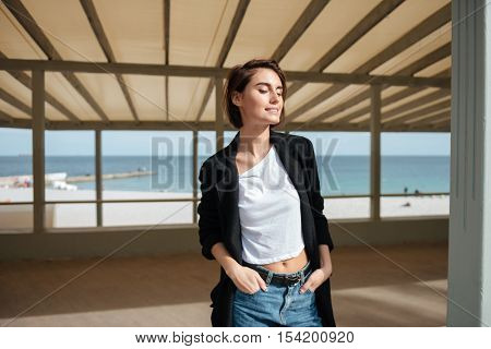 Cheerful attrative young woman standing in gazebo on the beach