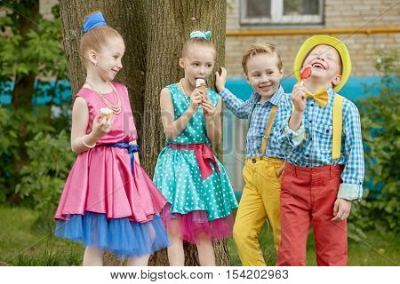 Four children stand outdoot on summer day. Three of them eat icecream, one boy laughs.