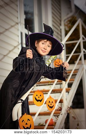 A boy in a costume of wizard with his magic wand is going to a halloween party. Trick or treat. Halloween concept.